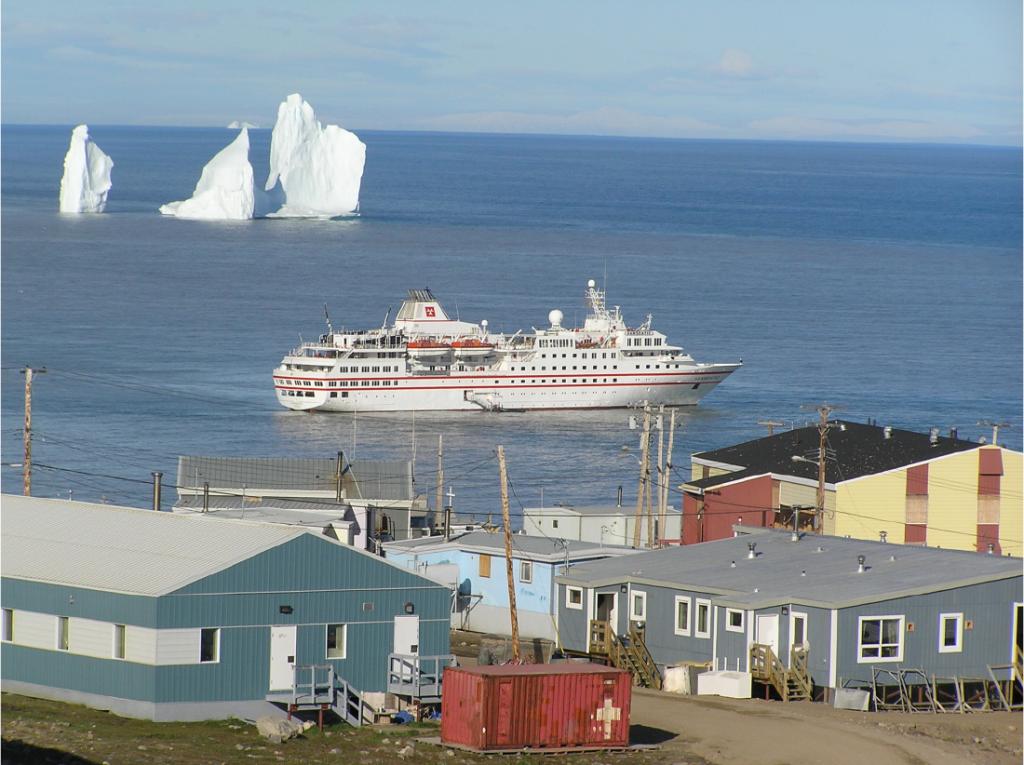 Photographie montrant le grand navire de croisière Hanseatic arrivant au village arctique de Pond Inlet (Nunavut) un jour d'été.