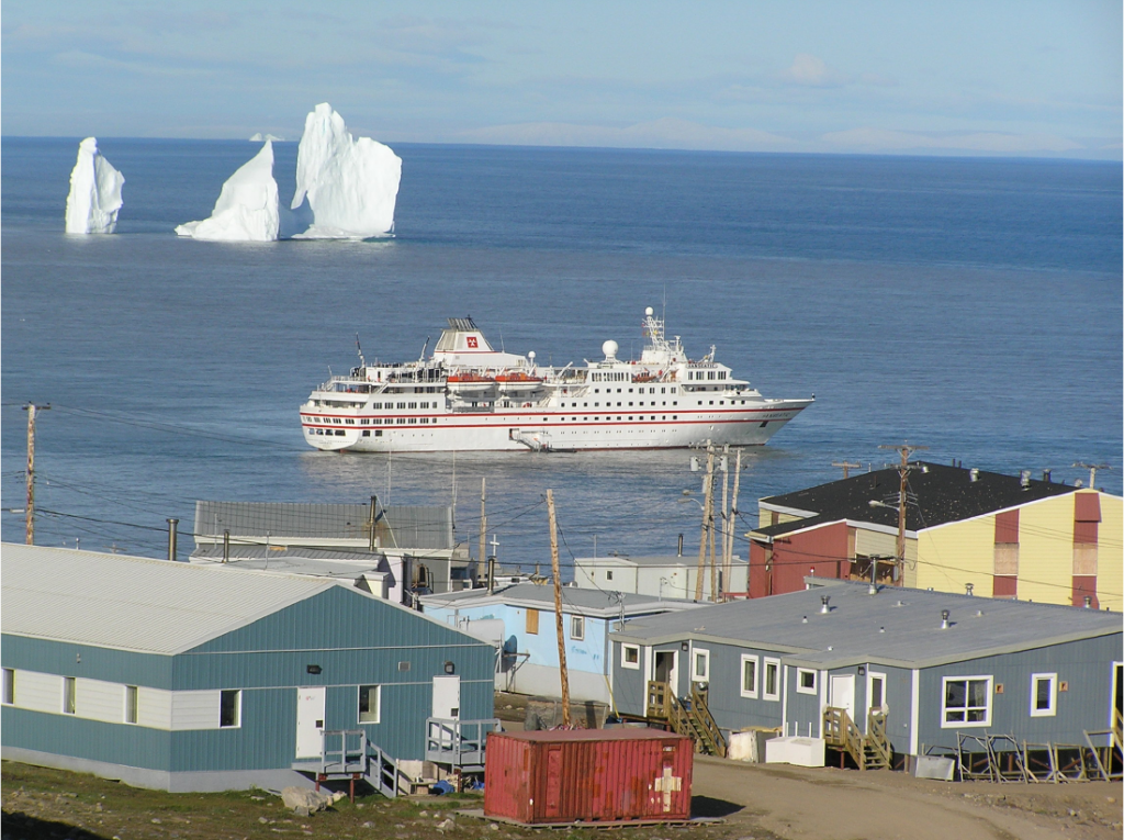 Photograph showing the large cruise ship, Hanseatic, arriving in the arctic town of Pond Inlet, Nunavut on a summer day.