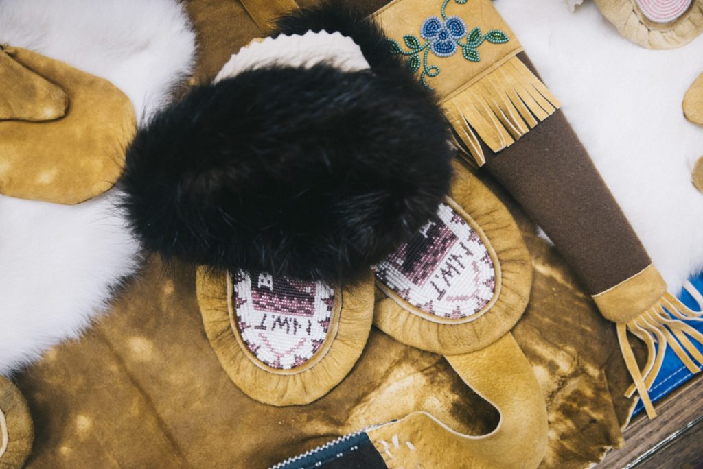 Photograph of clothing and tools made by artisans in Wekweètı̀ from tanned Caribou hide.